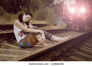 beautiful girl with flowers sitting on the tracks before the train
