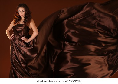Beautiful girl in a flowing satin brown cloth