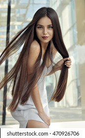 Beautiful girl with flying hair in the wind. She has long hair and well-groomed skin. Portrait on the background of modern architecture of metal and glass.