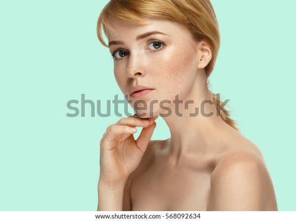 Beautiful girl freckles face blonde hair on summer green trendy color background.