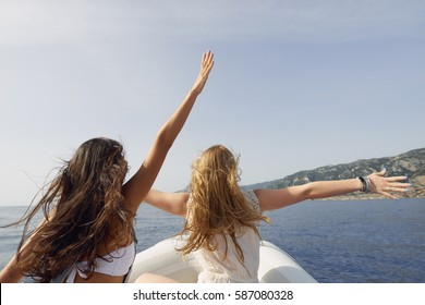Beautiful girl friends arms raised travel on speed boat to paradise island for relaxing nature tourist destination vacation discover explore
