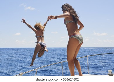 Beautiful Girl Friends jumping into deep blue sea from boat wild free healthy lifestyle on fun travel adventure vacation