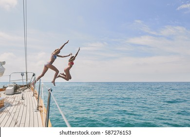 Beautiful girl friends jumping into blue sea from luxury wooden sailboat fun happy lifestyle ocean vacation travel