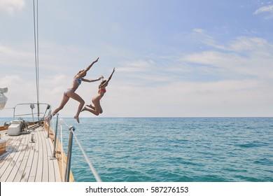 Schöne Mädchen Freunde springen in blaues Meer aus Luxus-Segelboot Spaß Lifestyle Seeblick Reisen