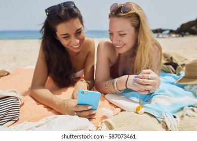 Beautiful girl friends using smart phone technology communication sharing on paradise beach destination summer wanderlust vacation