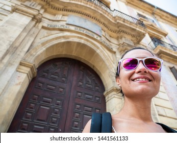 Beautiful girl in front of the Superior Court of Justice of the Valencian Community (Tribunal Superior de Justicia). Model dressed as a tourist, wearing sunglasses.