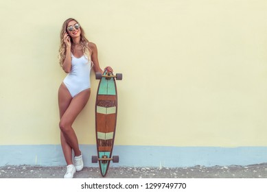 Beautiful girl in full growth, stands in summer against yellow wall. Woman White body Swimsuit Talking On Phone Happy Smiling. In hands board for skateboarding, longboard. Free space for text.