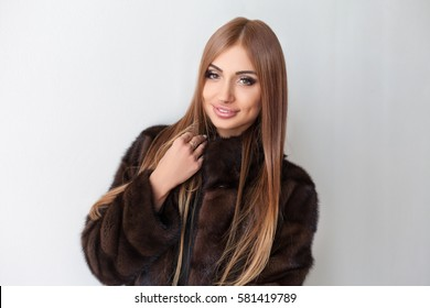 beautiful girl in a fur coat on a white background