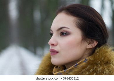 Beautiful girl in a fur coat and a yellow scarf on a background of a winter alley.