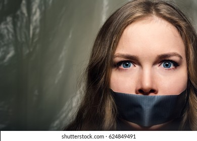 A beautiful girl with a gag in her mouth as a symbol of censorship. Silence of issues of sexual discrimination.