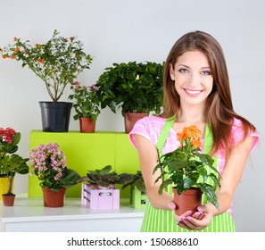 Beautiful girl gardener with flowers on grey background