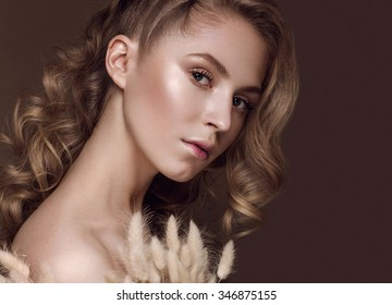 Beautiful girl with a gentle make-up and hairstyle with ears of corn in her hands. Beauty face. Picture taken in the studio.
