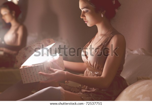 Beautiful girl with a gift in the room at night
