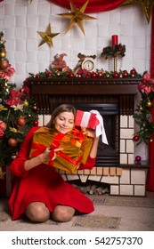 Beautiful girl with gifts in a red dress near a Christmas tree winter New year holiday.