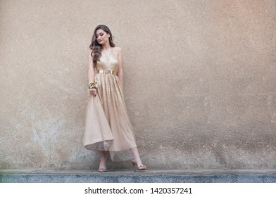 Beautiful girl in glamorous golden dress standing by the wall.