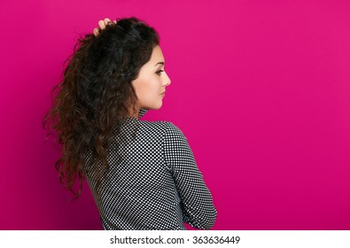 beautiful girl glamour portrait on pink background, long curly hair