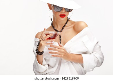Beautiful girl with a glass of red wine in her hand in an elegant white hat, sunglasses and exquisite jewelry.