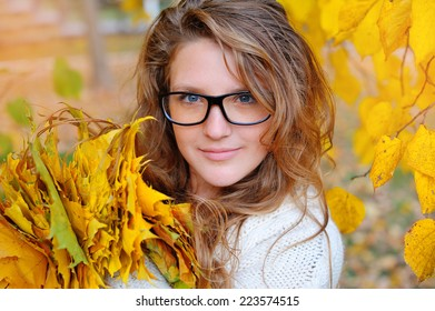 beautiful girl with glasses in autumn park with leaves.