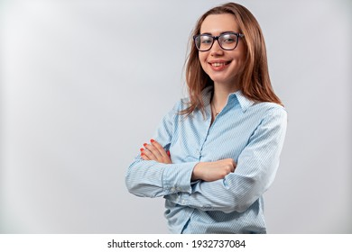 beautiful girl in glasses and a blue shirt on a white background looks into the frame. isolated