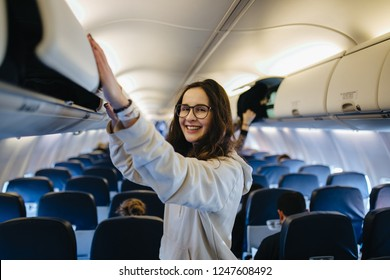Beautiful girl in glasses closing luggage compartment in the airplane.