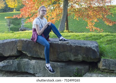 a beautiful girl in glasses is sitting quietly on the stones in a relaxed pose, the autumn season