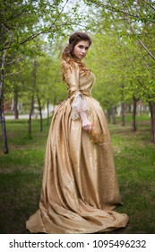 Beautiful girl in a gold dress against a background of green trees. A woman in a ball gown of the Rococo era.
