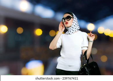 Beautiful girl with gold lights background. luxury, vintage girl with a bag walk around the store. Woman in sunglasses and a scarf with a female handbag shopping. Model girl in vintage retro style.