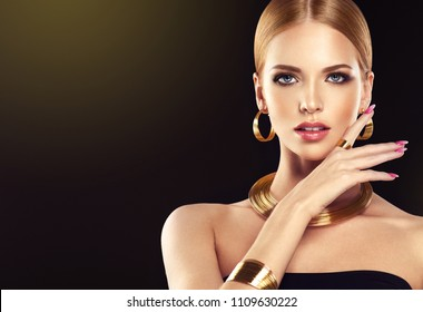 Beautiful girl with golden set jewelry .   Woman in a necklace with a ring, earrings and a bracelet. Beauty and accessories. Black background