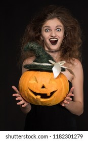 Beautiful girl with a gothic make-up as a witch smiles and holds an orange pumpkin on a black background for the holiday of Halloween