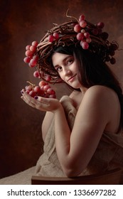 Beautiful girl with grapes. Vine wreath with grapes on a head.