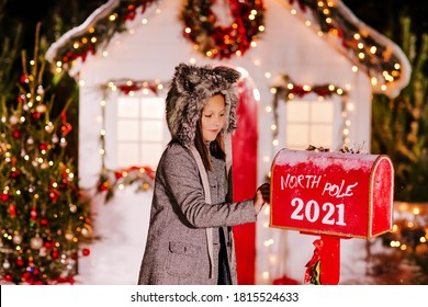 A beautiful girl in a gray coat and a furry gray wolf hat sends a letter to Santa in a red mailbox on the background of a Christmas decorated house. High quality photo