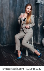 A beautiful girl in a gray suit is sitting on a chair in a Christmas decor. Toning