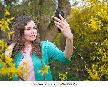 beautiful girl in green jacket making selfie among yellow blossom tree