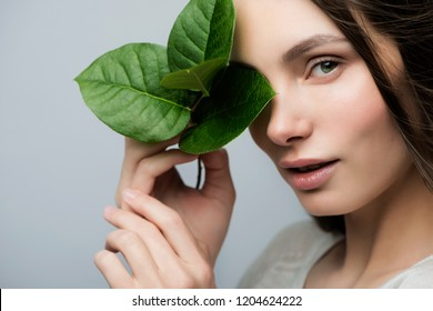 Beautiful girl with a green leaf in their hands