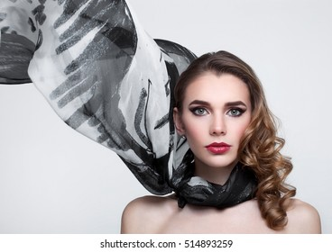 Beautiful girl with grey fashion scarf on grey background