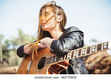 Beautiful  girl with a guitar sitting in the wind