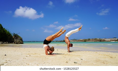 beautiful girl and guy acrobats do handstand on the white sand of the beach. couple in white doing acrobatic elements on the ocean on a sunny day. flexible back. back band pose
