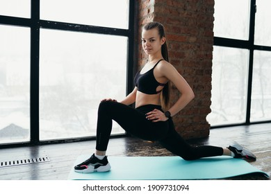Beautiful girl in the gym performs exercises for stretching the groin area.
