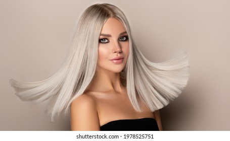 Beautiful girl with hair coloring in ultra blond. Stylish hairstyle done in a beauty salon. Fashion, cosmetics and makeup