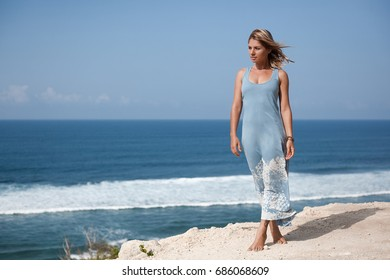 Beautiful girl with hair floating in the air and light-blue dress is standing on the rock ledge in front of the ocean and looking away