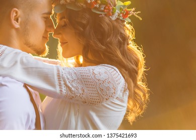 beautiful girl with a hairdo and a wreath on her head hugs a guy with a beard. sunlight and rays. close up