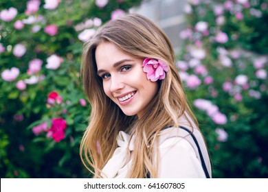 Beautiful girl with hairstyle and flower in hair smiling  looking at camera and standing near natural flower wall.