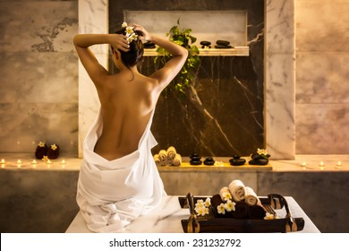 Beautiful girl in hammam. Tray with towels and flowers.
