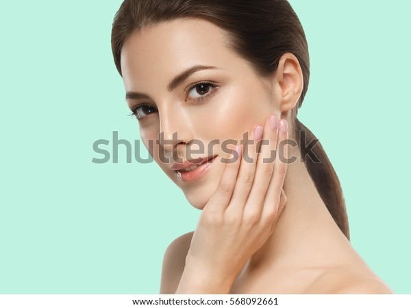 Beautiful girl hand touching face on summer green trendy color background.