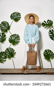 Beautiful girl with a handbag stands on a wooden platform in a studio on a background of a white wall with big green leaves. She wears a striped cyan shirt, white pants, brown shoes and a straw hat.