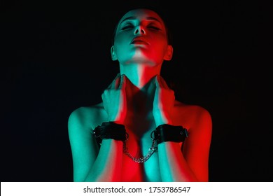 Schönes Mädchen in Handschellen. Schöne junge Frau in Farblichter. Kunstdesign, buntes Mädchen mit Radianzarote. gebundene Hände