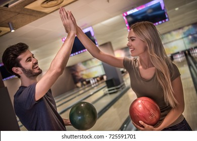 Beautiful girl and handsome guy are holding bowling balls, giving high five and smiling ready to play