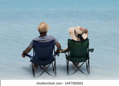 the beautiful girl and handsome man wearing wicker hats and sitting camp chairs in the lake and looking at the Salda lake from Turkey.