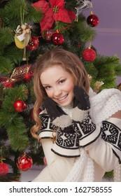 Beautiful girl hanging toy on Christmas tree