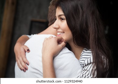 Beautiful girl happy being reconciled with boyfriend hugging her, millennial spouses embracing after serious fight, young husband cuddling wife excited about pregnancy news and becoming parents